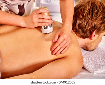 Man receiving electroporation back therapy at beauty salon.
