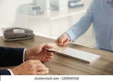 Man receiving money from teller at cash department window, closeup