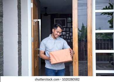 a man recieve a delivery box in front of his house door