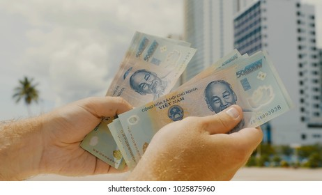 Man recounts Vietnamese money. Five hundred thousandth bills in the background of the city.