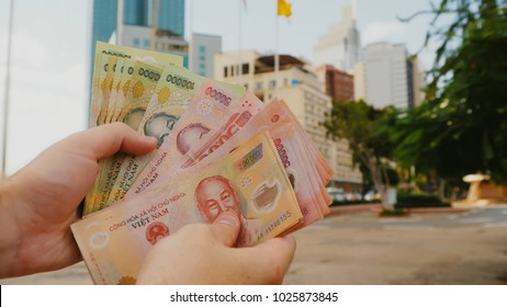 Man recounts Vietnamese money. Two hundred and one hundred thousandth of the banknote on the background of downtown Ho Chi Minh city.