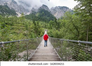 Man with red anorak crossing a suspension bridge in Nationalpark Berchtesgaden, Bavaria