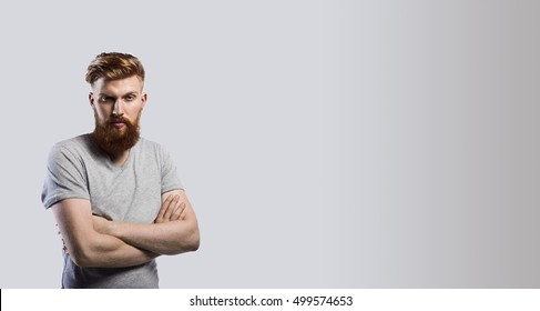 Man with red bearded stay in studio with crossed arms in grey t-shirt. Strong and brave guy on gradient background look to the camera. Copy space for advertising text.