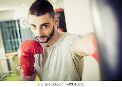 Man with red boxing gloves training on a punching bag in the gym