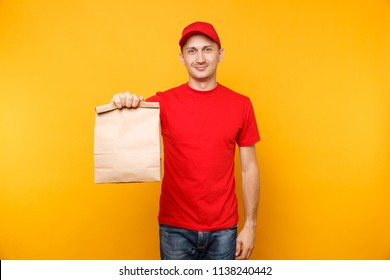 Man in red cap, t-shirt giving fast food order isolated on yellow background. Male employee courier hold empty paper packet with food. Products delivery from shop or restaurant to home. Copy space