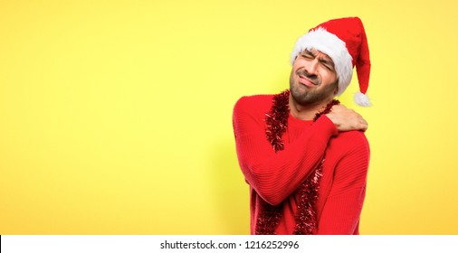 Man with red clothes celebrating the Christmas holidays suffering from pain in shoulder for having made an effort on yellow background