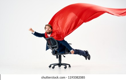 a man in a red coat riding on an office chair