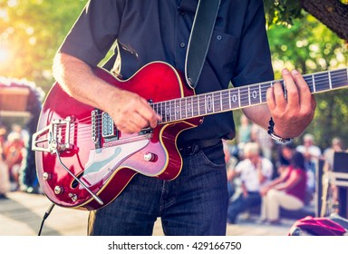 Man with a red electric guitar in the park playing a concert
