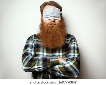 A man with a red hair and a red beard wearing a face mask over his eyes.  A bearded man with a protective mask worn in a funny way. Go crazy in the quarantine .
