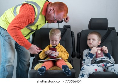 A man with red hair checks his passport. A happy little child is sitting in the car seat-belt. The concept of border security. Customs control.