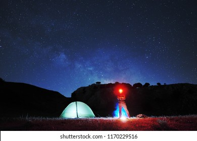 man with red headlamp looking in camera near lighting tent, on background starry sky above mountain of Nebrodi Park