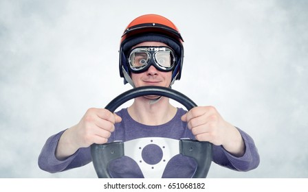 Man in red helmet and goggles with steering wheel. car driver concept