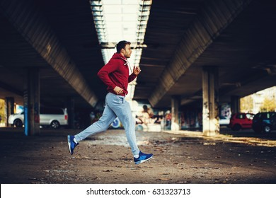 Man in red hoodie running under overpass