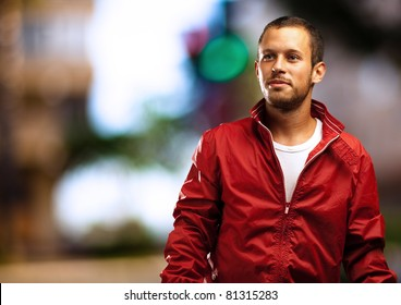 man with red jacket with a city as a background