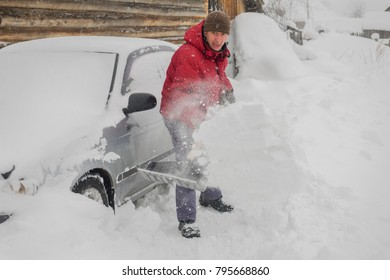 man in red jacket cleans black shovel snow near his car because it snowed a lot