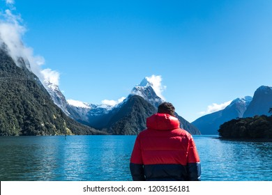 Man in red Jacket looking at beautiful scenery and Mountains in Milford Sound, New Zealand