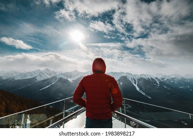 A man with a red jacket is looking at the Canadian Rockie mountains from the top of the Sulfur mountain in Banff, Canada