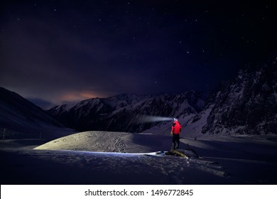 Man in red jacket with ray from his head light at starry night the mountain in ski resort at winter