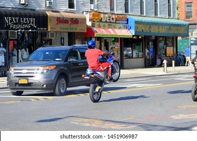 man in red on a blue and white mountain motor bike do wheelie on a bike on Fulton street in the crown heights Brooklyn July 15 2019