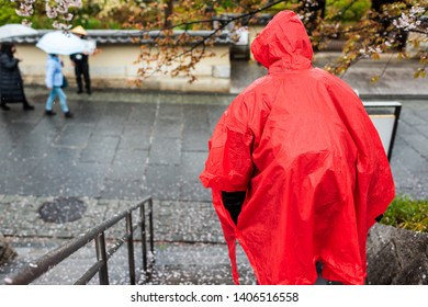 Man in red poncho walking down steps during rainy day on street road sidewalk near Gion and fallen cherry blossom flower petals