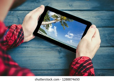 Man in red shirt holding tablet device over wooden table watching beautiful blue sky exotic summer landscape.