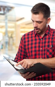 Man with red shirt over shopping center background. Looking surprised and holding a black folder