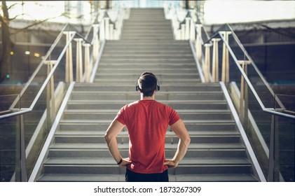 Man in red shirt preparing for stair run.