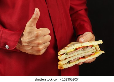 Man in red shirt recommends  and likes sandwich on a black background close up