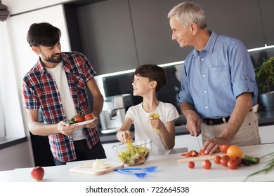 A man in a red shirt is standing with a plate on which vegetables lie, next to his son. who tears the leaves of the salad and his father, who cuts tomatoes