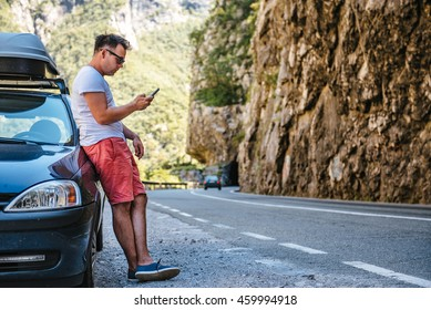 Man in red shorts standing by the Broke Down car and calling for help with smart phone