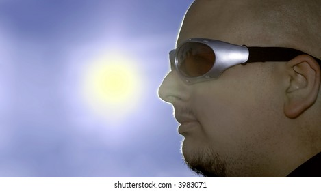 Man in red and silver glasses looking into the sun