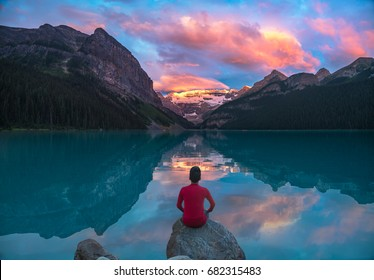 A man in red sit on rock watching Lake Louise in the morning sun light with colorful clouds and reflections