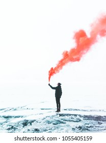 Man with red smoke bomb on the field