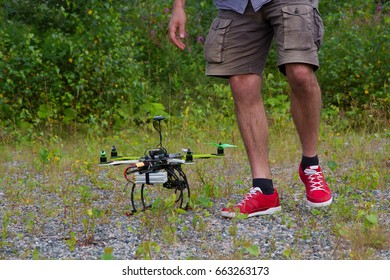 Man with red sneakers is walking to the drone in summer day. Drone with antenna is on the grass.