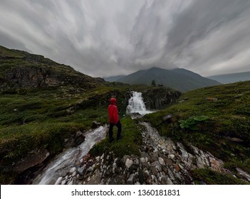 man in red stands under waterfall on black rock in mountains on cloudy rainy day.. Wide panorama