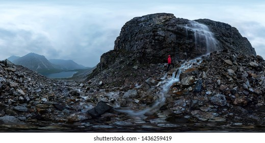 man in red stands under a waterfall on a black rock in the mountains on a cloudy rainy day. Spherical panorama 360vr