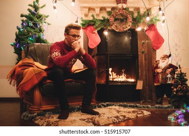 Man in red sweater sitting in front of the fireplace. Loneliness at New Year. Lots of scenery for the new year. Guy on the background of Christmas tree
