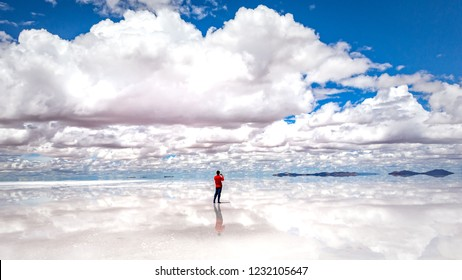 A man in a red sweater is walking among the reflected clouds and makes photo , mirror water surface  of Salar Uyuni , Bolivia, South America, wide format