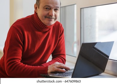 man in the red sweater working on the laptop by the window. Doing freelance in adulthood.