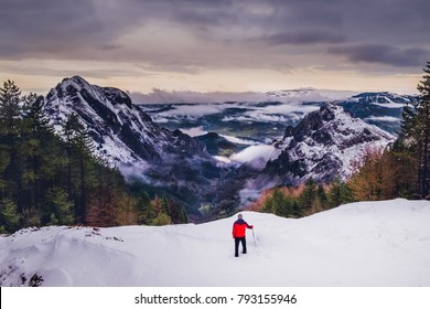 A man in red at the top of a mountain with snow