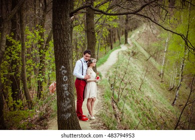 Man in red trousers and shoes hugs his lady from behind while standing in the park