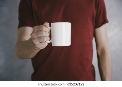 Man in red t-shirt holding big white coffee cup.Mock up of clean coffee cup.Horizontal mockup.