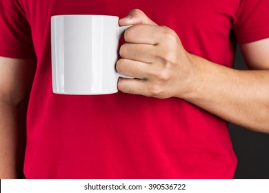 Man in red t-shirt holding Coffee mug with two hand