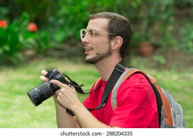 Man in red t-shirt looking up from camera with grassy background