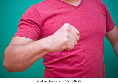 Man in red t-shirt showing fist