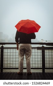 Man with a red umbrella looking out over the East River on a rainy day