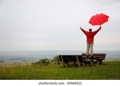 Man with red umbrella at a rainy day raising his arms