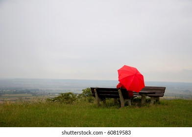 Man with red umbrella sitting on a bench
