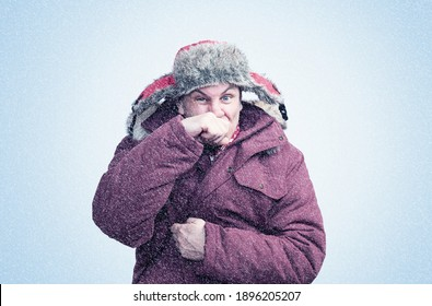 A man in red winter clothes wipes his nose with his hand in the cold, snow is falling around