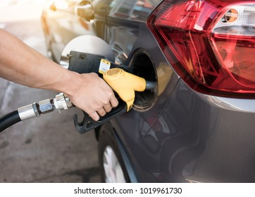 Man refilling gasoline oil with fuel at the refuel station
